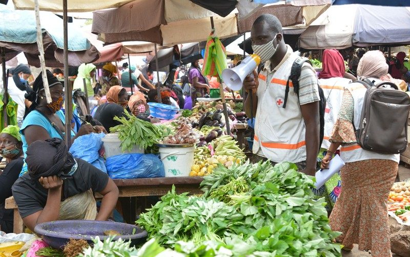 A man in a face mask talks through a megaphone to people at market stalls piled with vegetables.