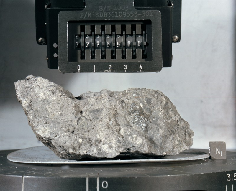 A piece of rock on a display stand in a safe.