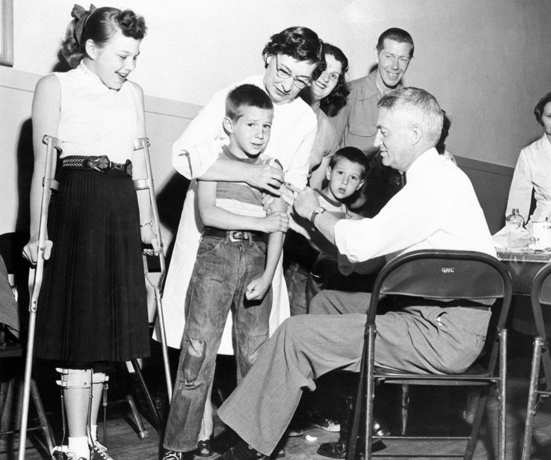 Black and white photo of a boy receiving an injection in the arm as other people watch.