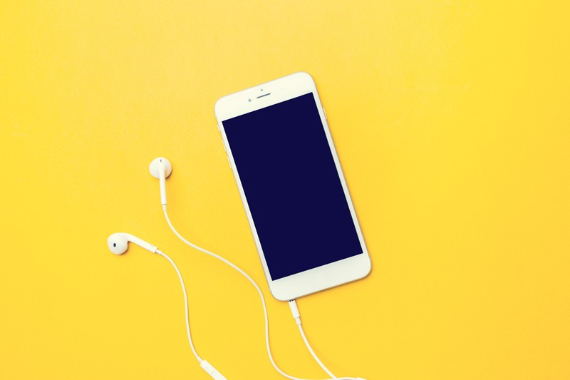 Smart phone with hands-free kit on yellow background
