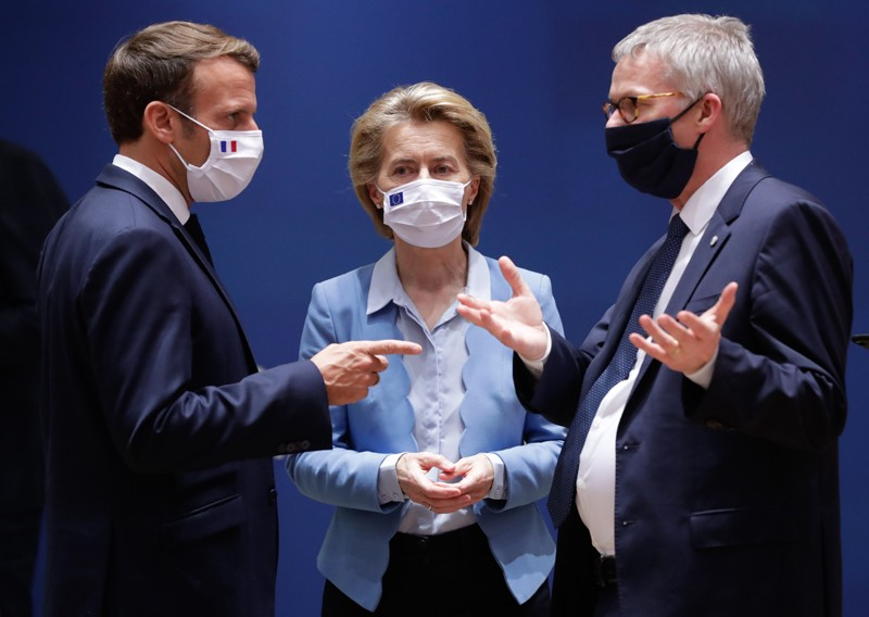 Three people wearing facing masks, standing close together and talking.