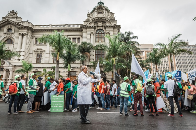 Salim Abdool Karim, wearing a white coat and holding a megaphone, leads a crowd of demonstrators in Durban, South Africa