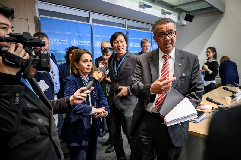 WHO Director-General Tedros Adhanom Ghebreyesus is surrounded by journalists