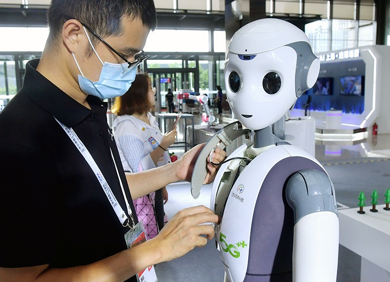 A staff member adjusts a robot at a display.