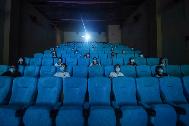 People wearing face masks sitting apart for social distancing at a cinema in Hangzhou, China
