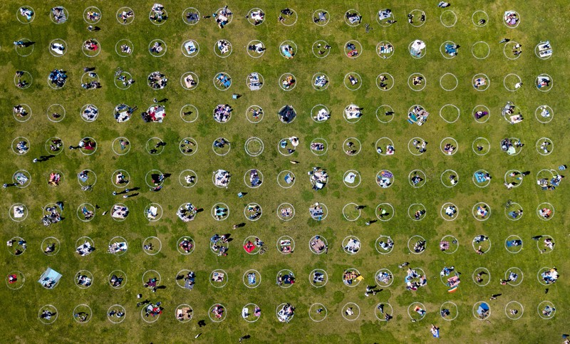 Aerial shot of people gathered inside painted circles on the grass encouraging social distancing in a San Francisco park
