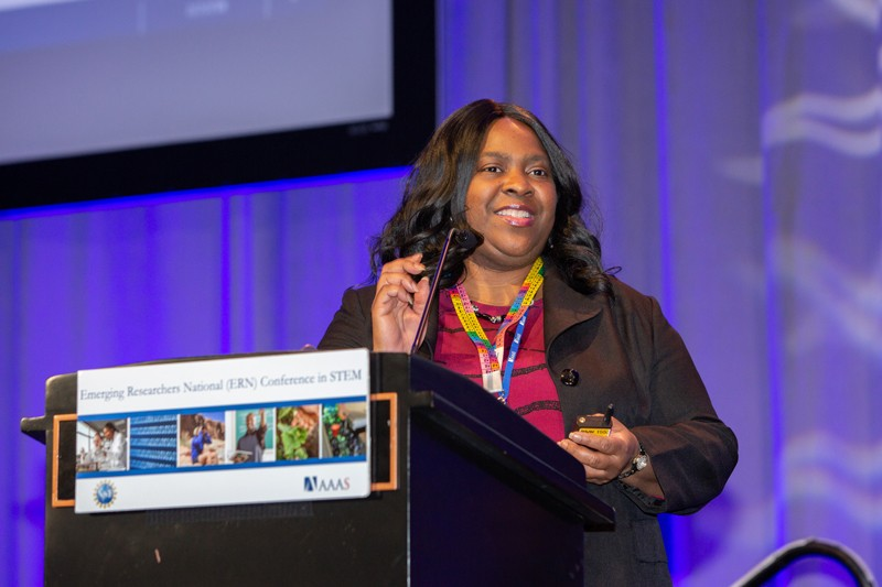 A woman speaking at a podium marked Emerging Researchers National Conference in STEM.