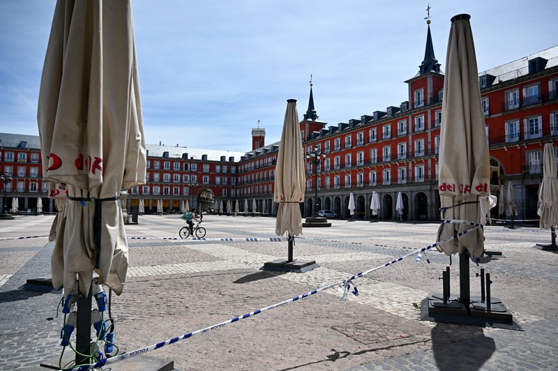 A cyclist rides their bike next to the terrace of a closed restaurant in Madrid's Plaza Mayor