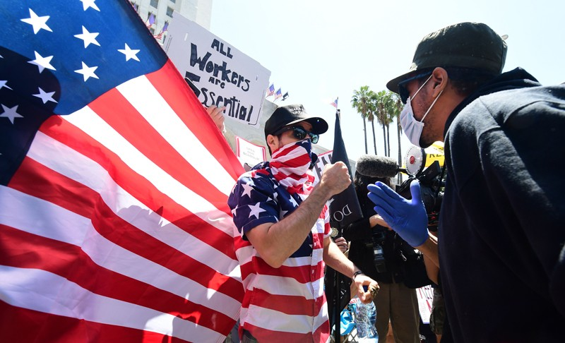 Two opposing protesters wearing face masks argue during a demonstration, one wears an American flag shirt
