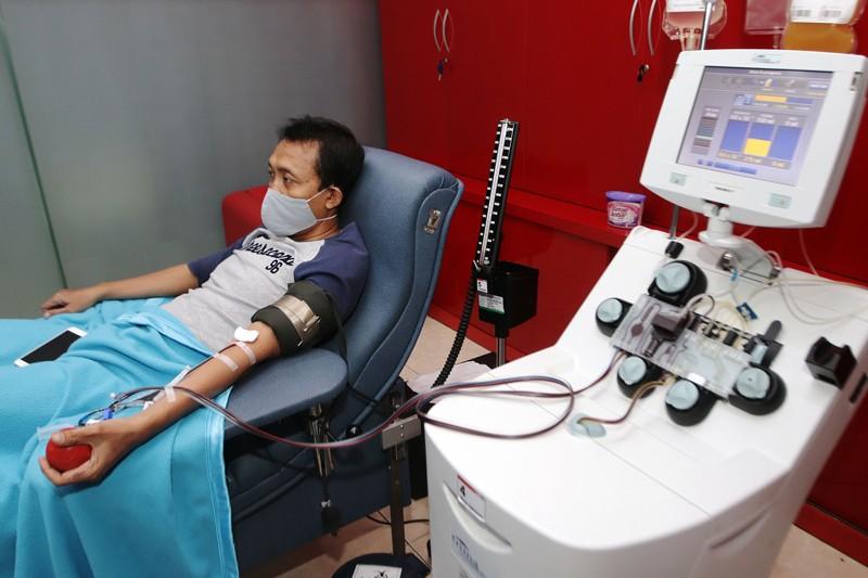 A man wearing a face mask sits in a hospital bed while blood is drawn from his arm and plasma collected by apheresis apparatus.