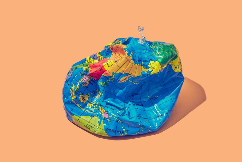 Deflated plastic Earth placed on an orange background.