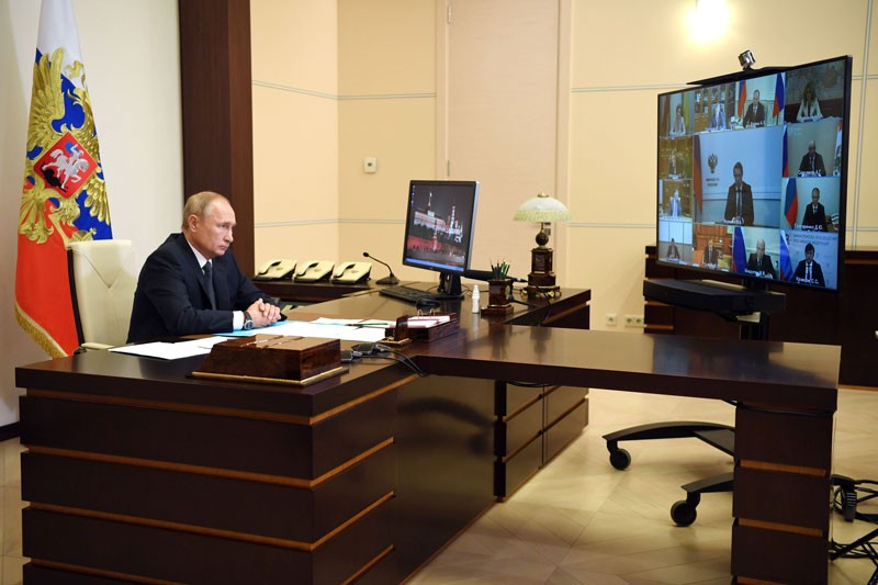 Vladimir Putin sitting at a large desk, watching a videoconference, with a flag behind him.