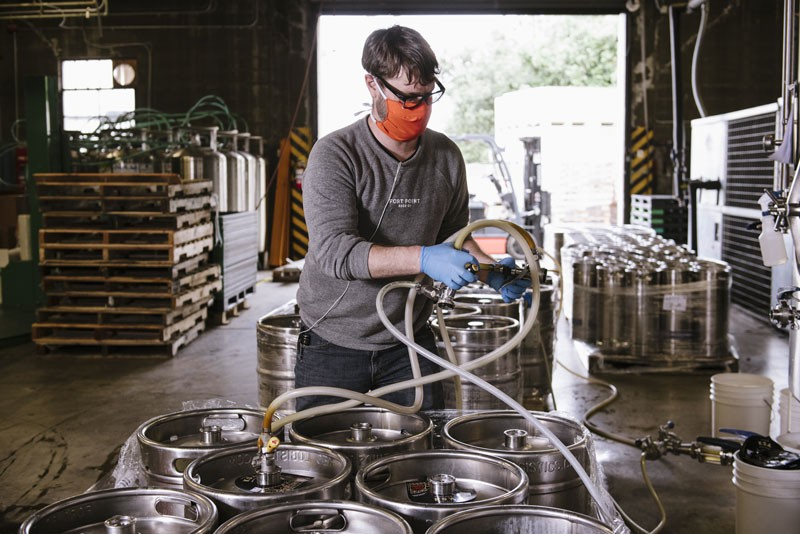 A worker wearing a protective mask arranges hoses while emptying half-barrel kegs of beer