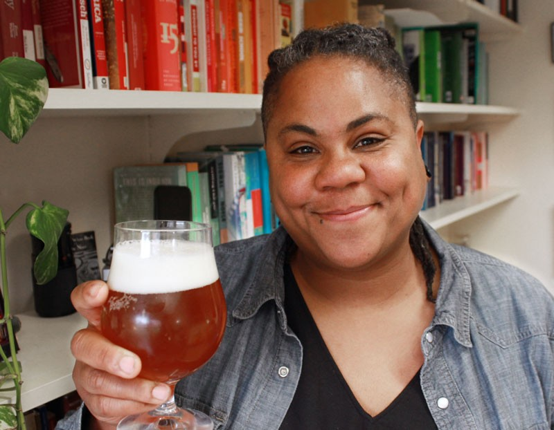 A woman raises a glass of beer and smiles at the camera.