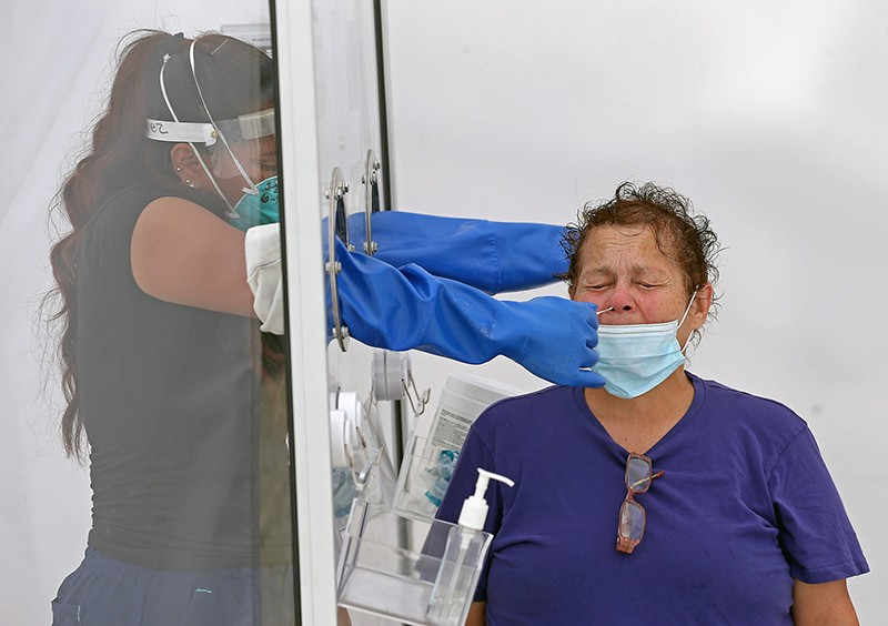 A woman has her nose swabbed through a plastic screen by a health worker wearing a visor, mask and gloves