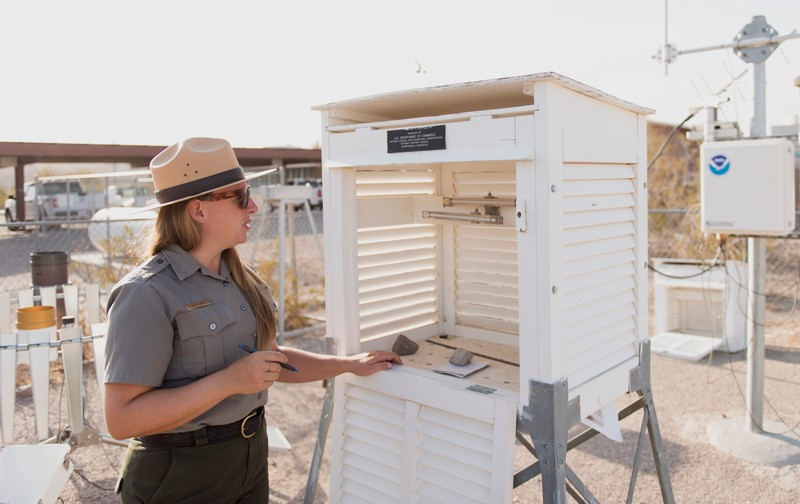 A Park Ranger checks the thermometers inside the Stevenson screen at a weather station in Death Valley