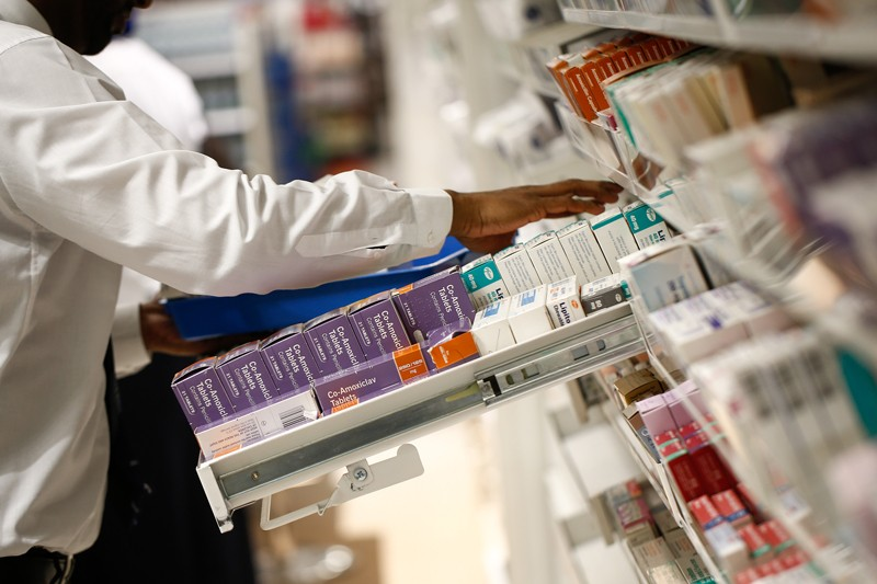 A pharmacist looks through a draw of boxed medications