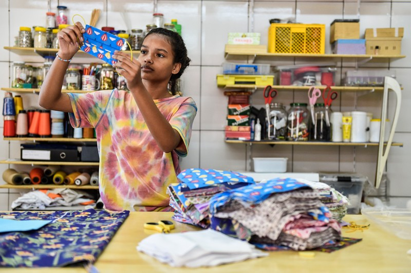 A young woman in a tie-dye t-shirt holds up a face mask in a workshop in Rio de Janeiro where face masks are being produced