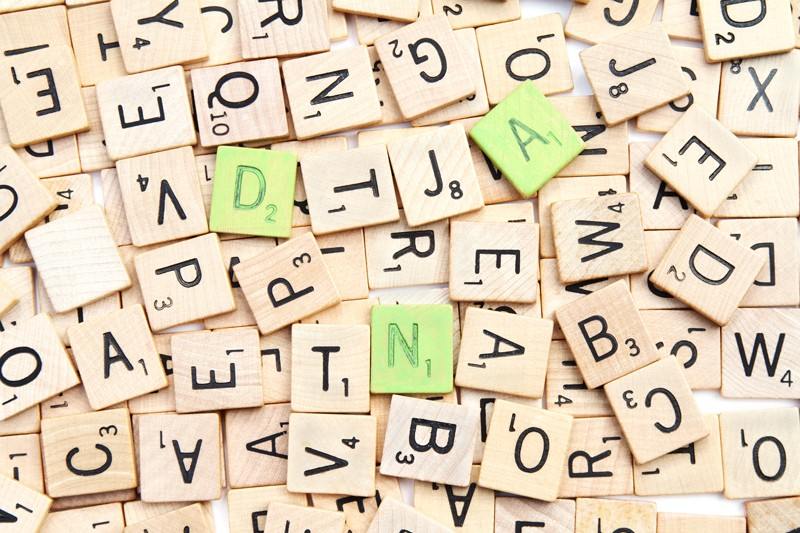 Scrabble tiles with three painted green letters spelling DNA scattered on a pile of random letters