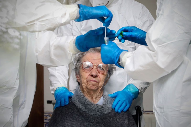 An elderly woman undergoes COVID-19 screening tests