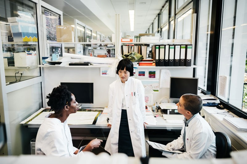 Three female scientists of different races talk together in a laboratory.