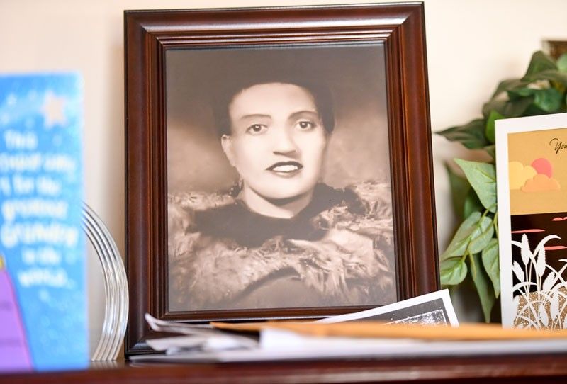 A framed photo of Henrietta Lacks sits in a living room