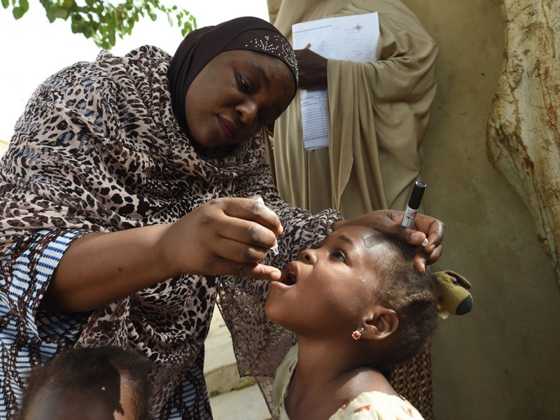 NICEF health consultant Hadiza Waya tries to immunise a child during vaccination campaign against polio, Nigeria.