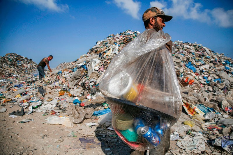A Palestinian garbage collector walks with a bag of trash