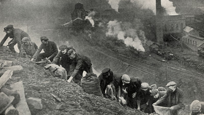 A line of unemployed men carrying sacks search for lumps of coal on a slag heap in South Wales