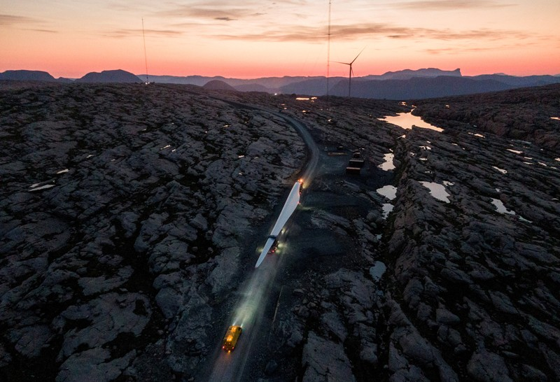 A large wind turbine blade is transported by road through a rocky landscape at sunset with a wind turbine in the distance