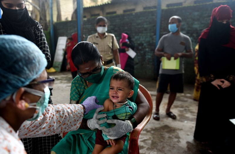 A BMC healthcare worker giving a vaccination to a small child in Mumbai