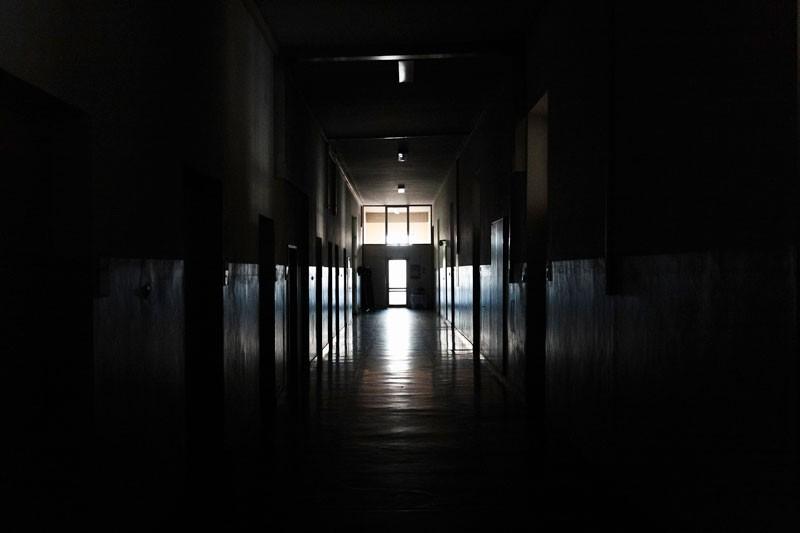 Light shining from a door in a dark hallway
