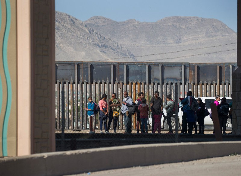 Migrants wait in line in front of a large fence at the US-Mexico border with hills in the background