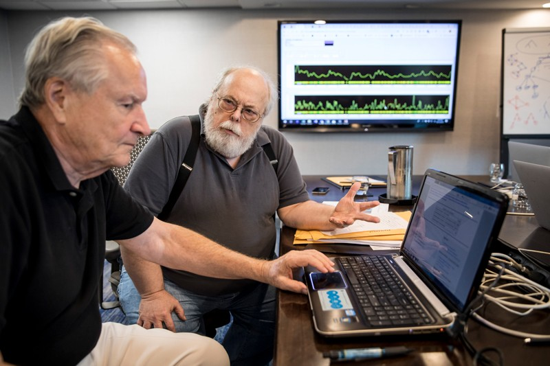 Curtis Rogers and John Olson look at a laptop with a large screen showing data charts on the wall behind