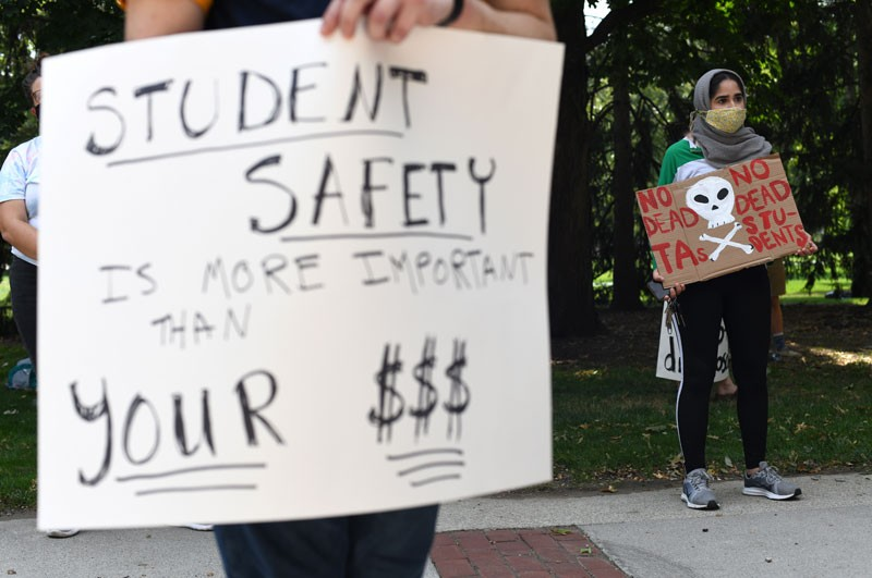 Members of the Ohio State University Graduate Student Labor Coalition hold signs during a protest