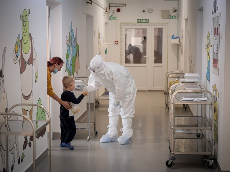 A child wearing black talks to a person in full protective gear, in a hospital corridor decorated with cartoon characte
