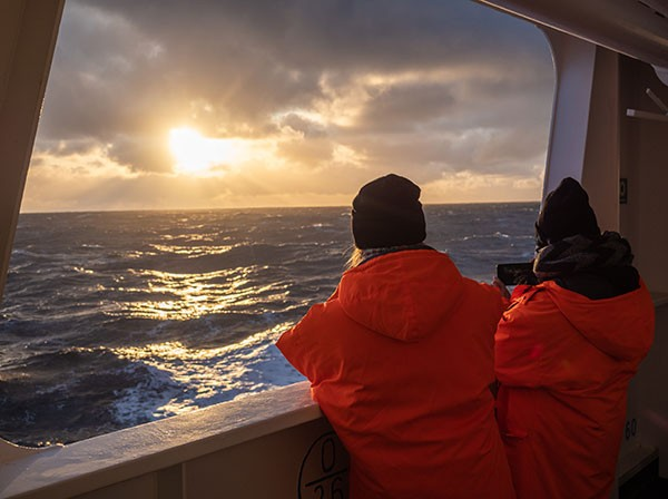 Two people look out to sea from the Akademik Fedorov in 2019