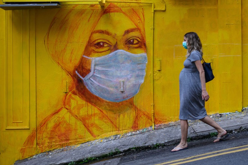 A pregnant woman wearing a face mask walks past a street mural in Hong Kong