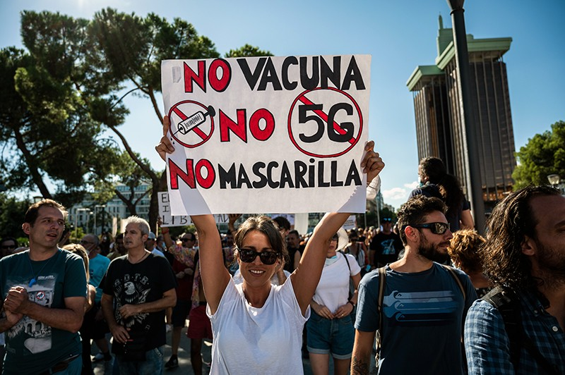 A protestor holds a sign against the use of vaccine, 5G and mask wearing in Spain