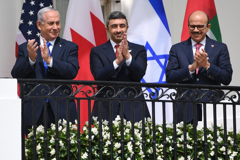 Three men in suits applauding on a balcony, standing in front of the flags of the United States, Bahrain, Israel and the UAE.