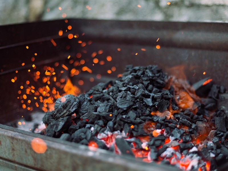 Close-up of charcoal burning In barbecue grill.