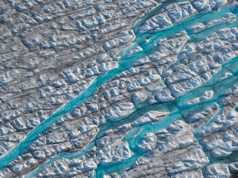 Figure 1: In this view from an airplane rivers of meltwater carve into the Greenland ice sheet, near Ilulissat, Greenland.