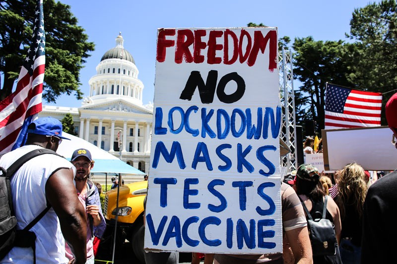 A protester holds a placard that says 'Freedom No Lockdown Masks Tests Vaccine'.