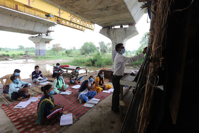 A university student conducts open-air classes in a slum for underprivileged students