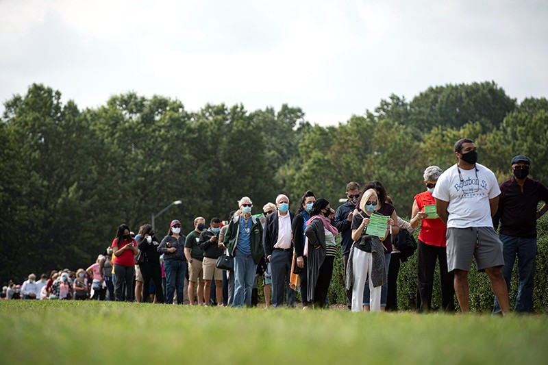 People wait in a socially distant line at an early voting site in Fairfax, Virginia