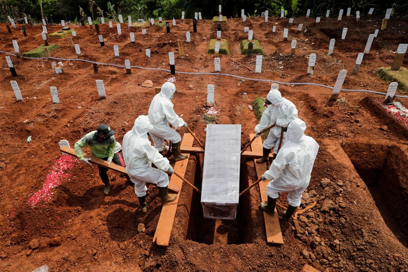 Workers clad in hazmat suits bury the coffin of a coronavirus victim