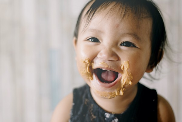 A young child with peanut butter smeared around her mouth