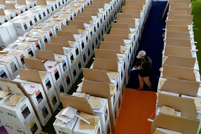 An official supervises ballot boxes for Indonesia's upcoming general election
