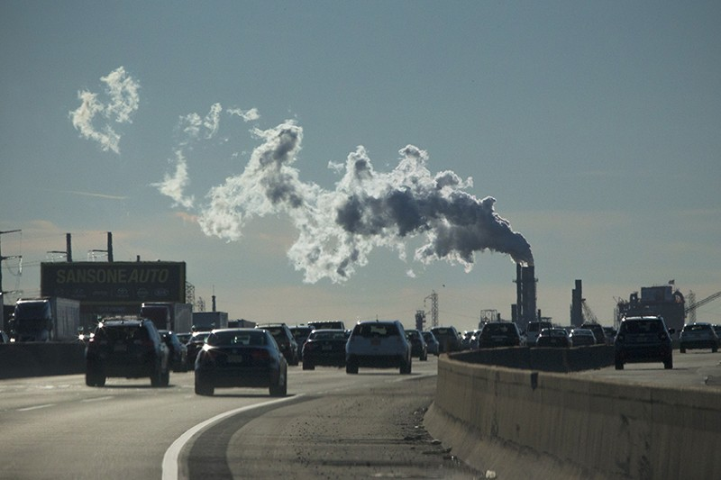 Cars on a turnpike pass a factory emitting smoke in New Jersey, U.S.