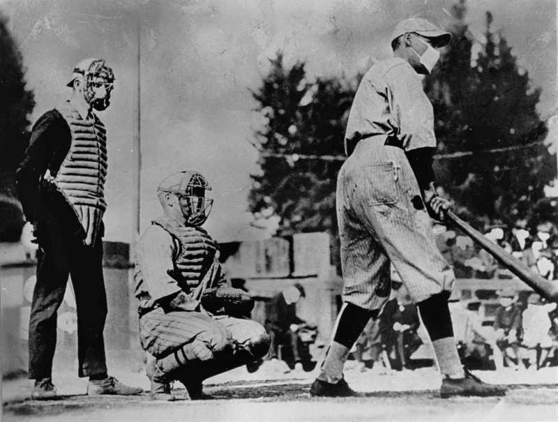 Jucători de baseball, un bătător și unul de prindere, și arbitru care stătea în spate, purtând măști în timpul pandemiei de gripă din 1918